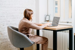 The correct position posture when working at the computer. A woman sits at a table with a laptop computer. Spinal curvature. Good posture. Healthy back.