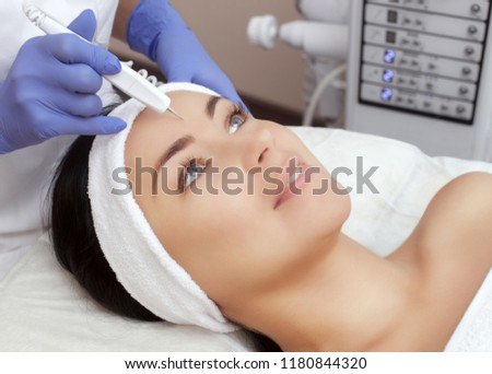 The cosmetologist makes the procedure treatment of Couperose of the facial skin of a beautiful, young woman in a beauty salon.Cosmetology and professional skin care. #1180844320