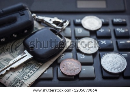 The cost of the car, the rise in gasoline prices, expensive maintenance. Keys and coins lie on the background of the calculator. The background is blurred.