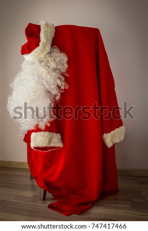 The costume of Santa Claus hangs on a chair. White beard, red hat and fur coat. Light background, vignetting. Vertical arrangement. #747417466