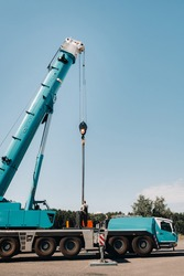 the counterweight is installed by an unrecognizable worker on a large blue car crane and is prepared to work on a site next to a large modern building. The largest truck crane for solving complex