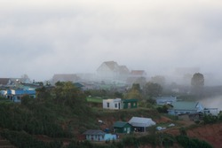 the countryside with small houses and farm. Background with magic dense fog and light of the sky and clouds at dawn