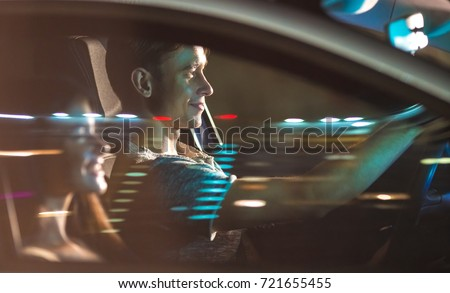 The couple drive a car. evening night time