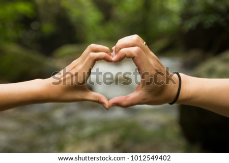 The couple hands combined heart shape sign of love on the river #1012549402