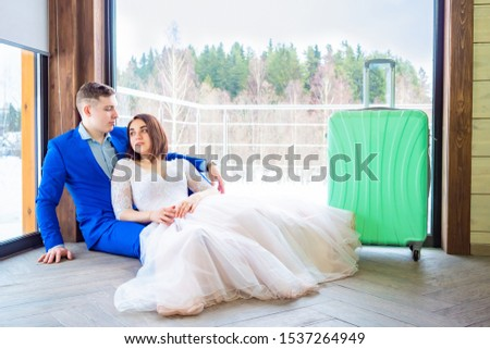 The couple in the cottage. The bride and groom came to rest in a country house. Winter wedding. Honeymoon. Honeymoon trip. Rest together.  Girl and man sitting on the floor in the cottage. #1537264949