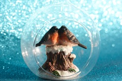 The couple of bullfinches sits on the snowy stump inside the glass transparent Christmas ball on a shining bokeh background. Christmas holiday concept