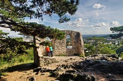 The couple rests on a tour of the castle ruins and looks out over the town of Modling. Tourism, hiking and travel concept. Moedling (Mödling), Lower Austria.Travel destination trip from Vienna.
