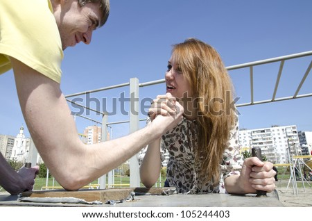 The couple, young man and woman in the heat of the fight - who in the family of the chief. Armwrestling - fight on their hands.