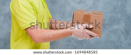 The courier holds cardboard boxes in disposable gloves. Contactless delivery during the quarantine period for coronavirus.