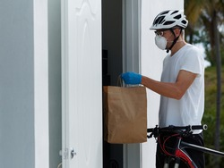 The courier in mask and gloves delivery food on a bicycle during a pandemic.