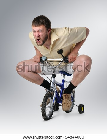 The courious man in shorts on a children's bicycle