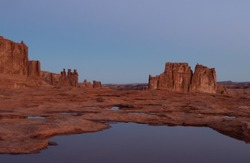 The Courthouse Towers and the Three Gossips Rock Formations in Arches National Park in Utah with a pond in the foreground.