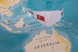 The COVID-19 Facial Mask with the Flag of East Timor Placed on a Map.