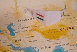 The COVID-19 Facial Mask with the Flag of Tajikistan Placed on a Map.