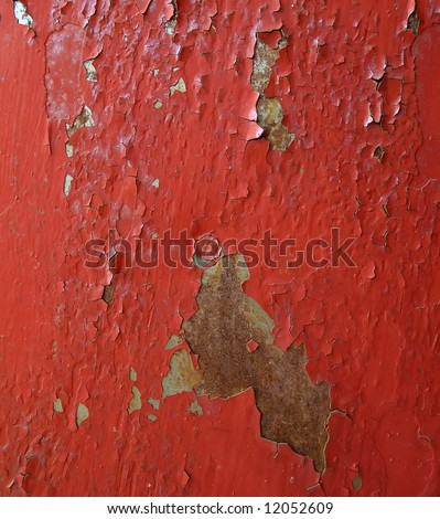 The cracked red paint on an old metallic surface.