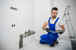 The craftsman attaches the tiles to the wall with cement. He is wearing a blue uniform and black gloves