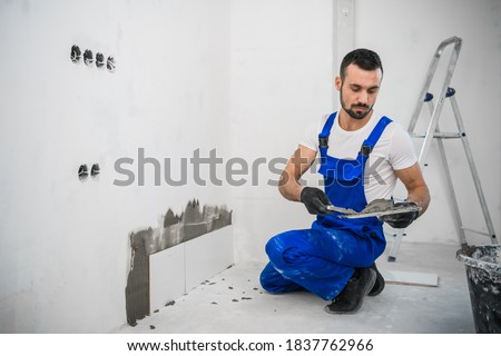 The craftsman attaches the tiles to the wall with cement. He is wearing a blue uniform and black gloves Stock photo ©