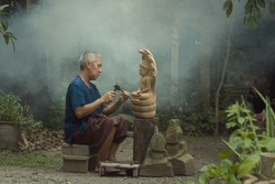 The craftsman concentrate to use the chisel carving the stone Buddha statue.