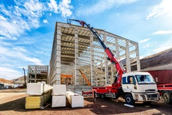 The crane ( HIAB ) extend its lift bucket to roof of the new building for isolation in the construction site. HIAB is a Swedish manufacturer of loader cranes, demountable container handlers, forestry.