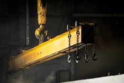 The crane moves a reinforced concrete product with holes.