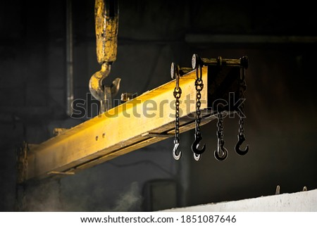 The crane moves a reinforced concrete product with holes.Reinforced concrete pillars fixed with metal hooks and chains on the background of the plant Foto stock ©