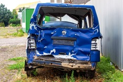 The crash car back view, broken minibus after accident. Failed blue van on country road, near a metal gray fence.