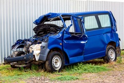 The crash car, broken minibus after accident. Failed blue van on country road, near a metal gray fence.