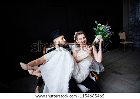 The creative bride with dreadlocks and a bouquet sits on the knees of the groom in a hat in a white vintage chair on a black background, a steep and amusing enamored couple #1154665465