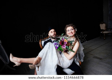 The creative bride with dreadlocks and a bouquet sits on the knees of the groom in a hat in a white vintage chair on a black background, a steep and amusing enamored couple #1154666878