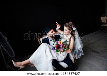 The creative bride with dreadlocks and a bouquet sits on the knees of the groom in a hat in a white vintage chair on a black background, a steep and amusing enamored couple #1154667427