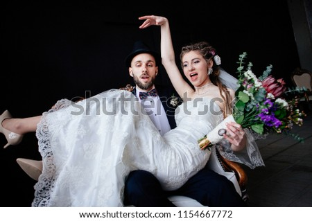 The creative bride with dreadlocks and a bouquet sits on the knees of the groom in a hat in a white vintage chair on a black background, a steep and amusing enamored couple #1154667772