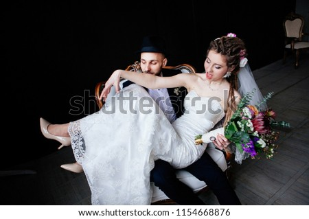 The creative bride with dreadlocks and a bouquet sits on the knees of the groom in a hat in a white vintage chair on a black background, a steep and amusing enamored couple #1154668876