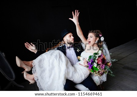 The creative bride with dreadlocks and a bouquet sits on the knees of the groom in a hat in a white vintage chair on a black background, a steep and amusing enamored couple #1154669461