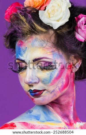 The creative, bright, color makeup. Floral makeup. Art makeup. Beautifully painted lips and eyes. Tone, powder, make-up. Multi-colored roses in her hair girl.