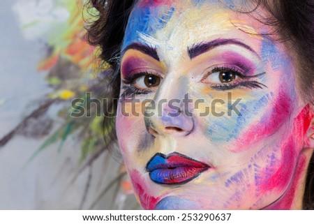 The creative, bright, color makeup. Floral makeup. Art makeup. Tone, powder, make-up. Multi-colored roses in her hair girl. Creative floral make-up on the model, background floral pattern.