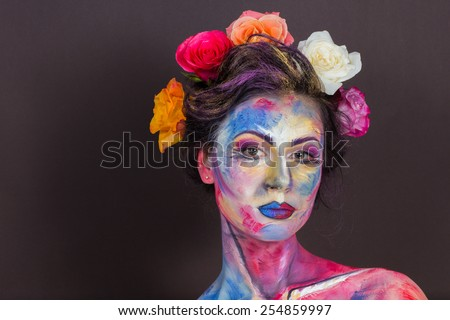 The creative, bright, color makeup. Floral makeup. Art makeup. Tone, powder, make-up. Multi-colored roses in her hair girl. Creative floral makeup on the model, background floral pattern.
