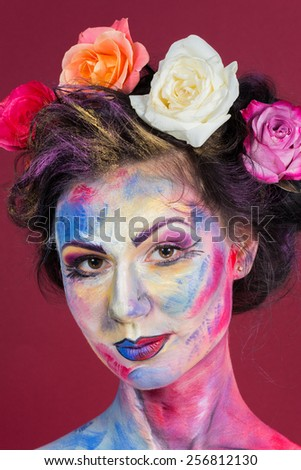 The creative, bright, color makeup. Floral makeup. Art makeup. Tone, powder, make-up. Multi-colored roses in her hair girl. Creative floral make-up on the model.