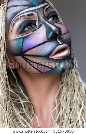 The creative, bright, graphic makeup.  Art makeup. Different colors wild look with braids. Young beautiful model with face art.
