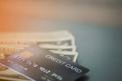 The credit card is placed on top of the dollar bill. All are placed on the table, close-up view.Concept spending money.