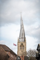 The Crooked Spire Church of St Marys in Chesterfield market town Derbyshire with Great Britain Union Jack flag flying in of famous twisted ancient steeple foreground