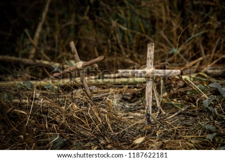 The cross is made of old wood and has a rope tied at the core in dry forest cemetery on dark background.