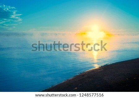 The cross of Jesus in a tranquil ocean seascape,drawn by the rays of the rising sun #1248577516