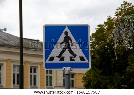 The crosswalk signs in Sweden consists of a blue square with a white triangle. Inside the triangle the silhoutte of a man walking across the road is depicted. #1560159509