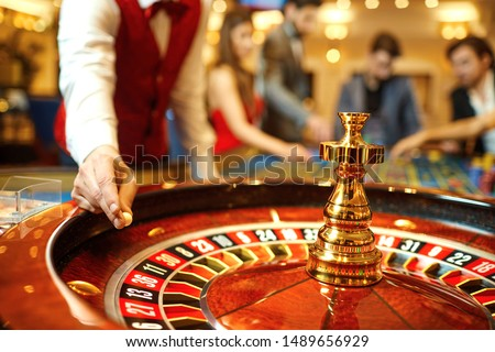 The croupier holds a roulette ball in a casino in his hand. Photo stock ©