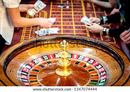 The croupier pays the winnings. Roulette. Gambling People make bets in casinos. A table with a tape measure. Lose money