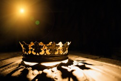 The crown on a black background is illuminated by a golden beam. Low-key image of a beautiful queen / royal crown Vintage is filtered. Fantasy of the medieval period. Battle for the Throne.