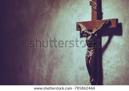 The Crucifix of Jesus Christ hanged on gray concrete wall background with copy space for your text, christian background