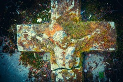 The crucifixion of Jesus Christ against gray stone slab. Fragment of very old stone partially destroyed statue in moss.