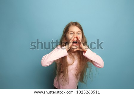 The cry. The angry screaming teen girl on a blue studio background. Facial expressions and people emotions concept. Trendy colors. Front view. Half-length portrait #1025268511