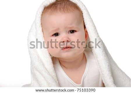 The crying baby under a towel. Age of 8 months. It is isolated on a white background